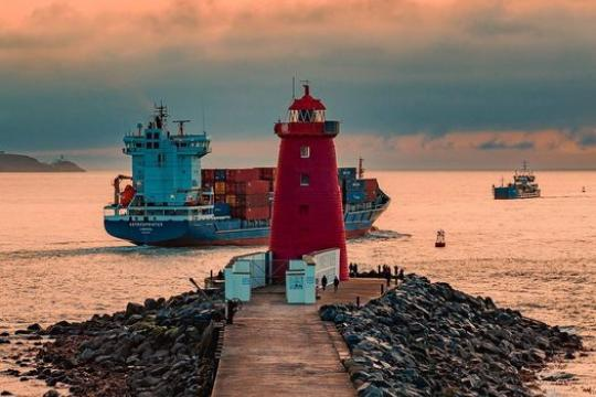 A cargo ship passing a red lighthouse at the entrance to Dublin port