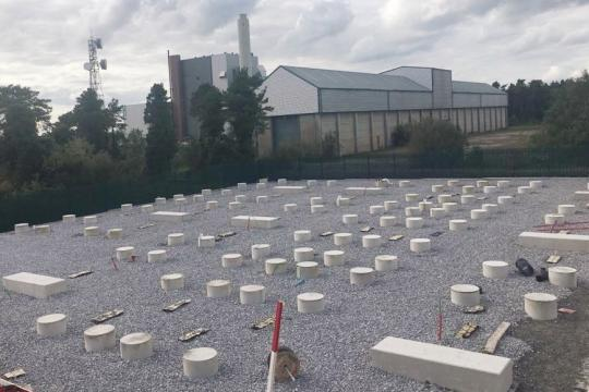 Building site showing circular concrete plinths as foundations for energy storage units