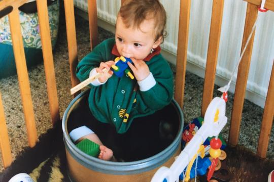Rob Lee as a baby in a fibre drum inside a playpen