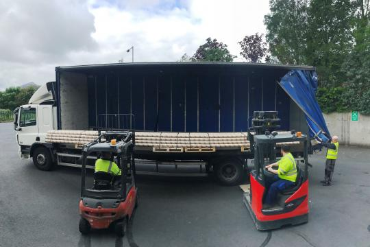 Extra long cardboard tubes being loaded by two forklifts onto a truck