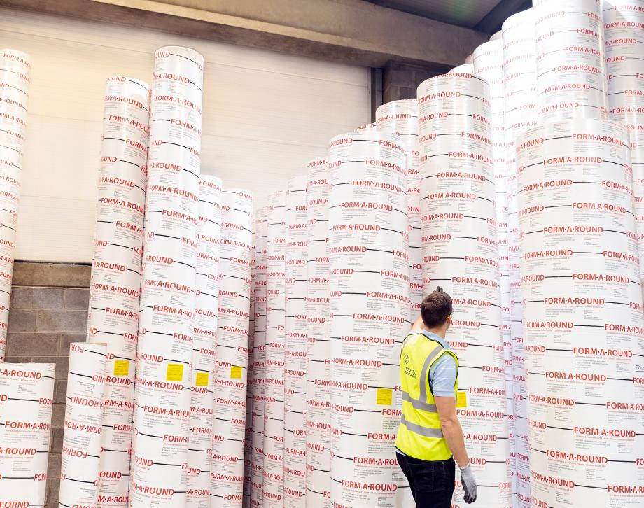 A factory worker with cardboard column moulds towering above him