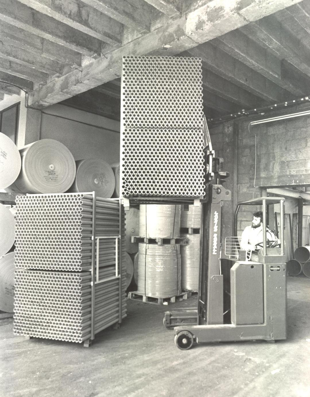 A forklift worker in a factory with cardboard tubes