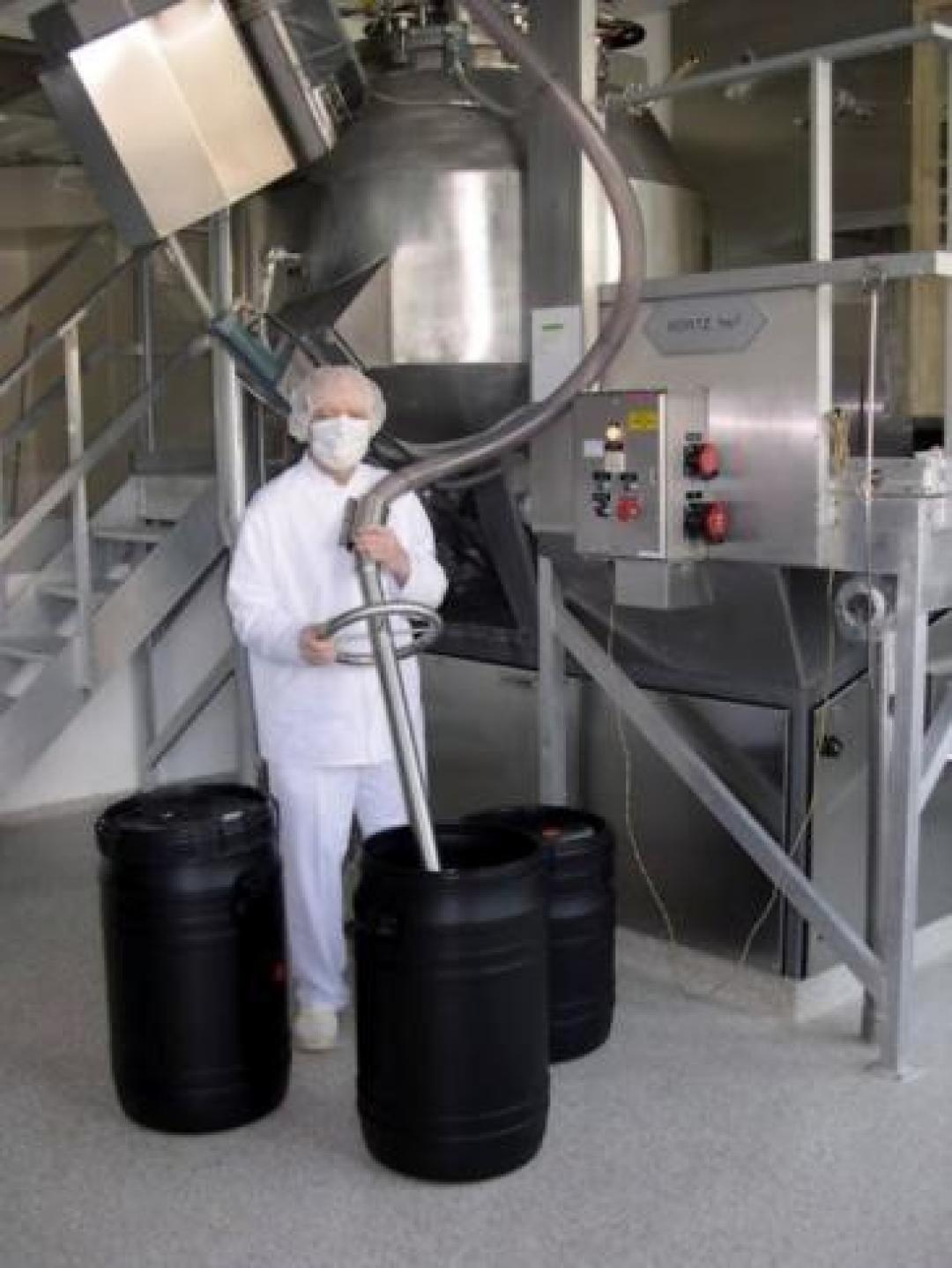 Operator in full PPE filling plastic conductive drum with dangerous product through hose