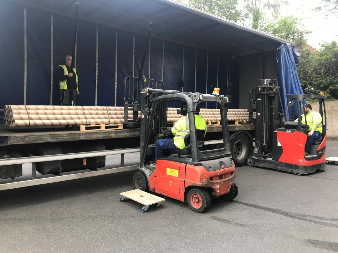 Two forklifts being used to place 8m long cardboard tubes into a lorry