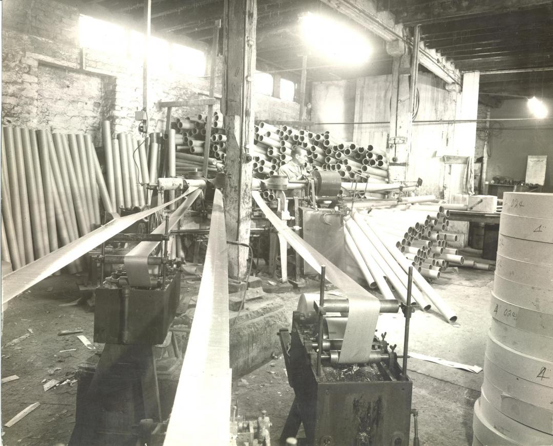 Black and white photo of old core winding machine in use