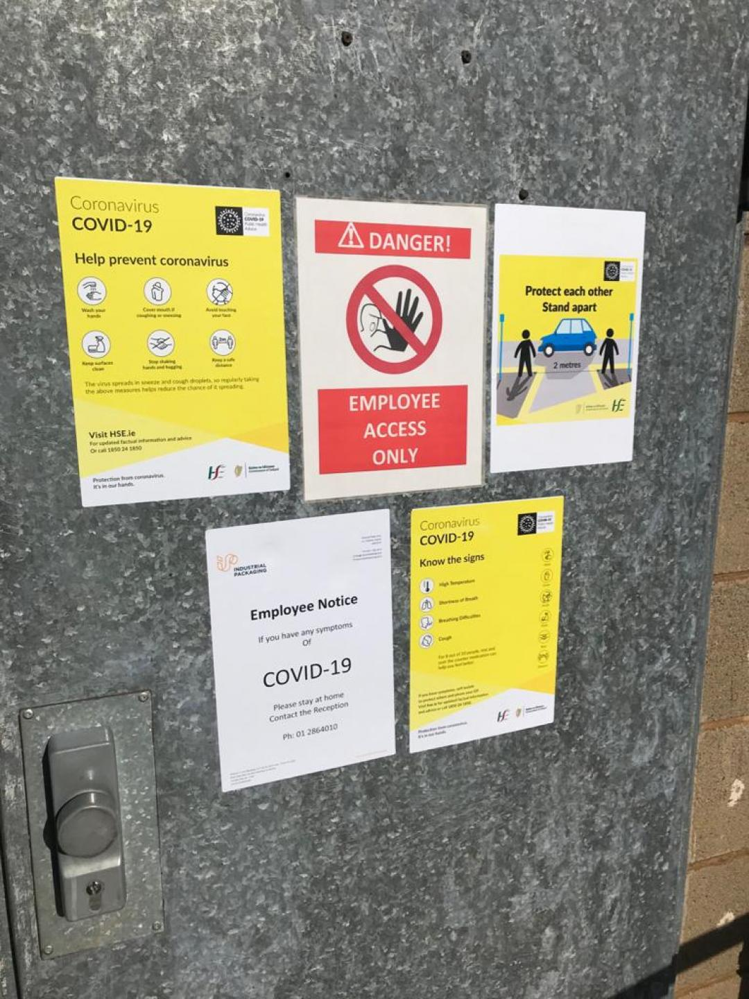 Signage on doors to Industrial Packaging factory about COVID19 safety measures