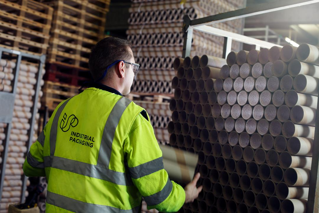 A factory operator in safetywear loads postal tubes on to a pallet