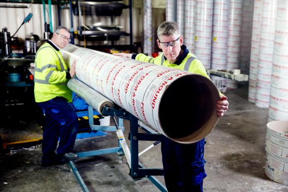 Two factory operators work together to manufacture a cardboard column mould