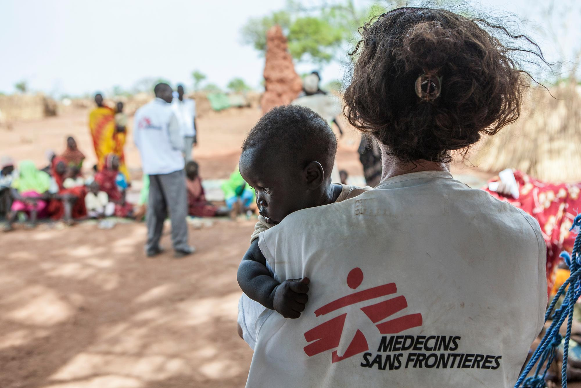 Adult wearing MSF charity branded jacket holding a toddler