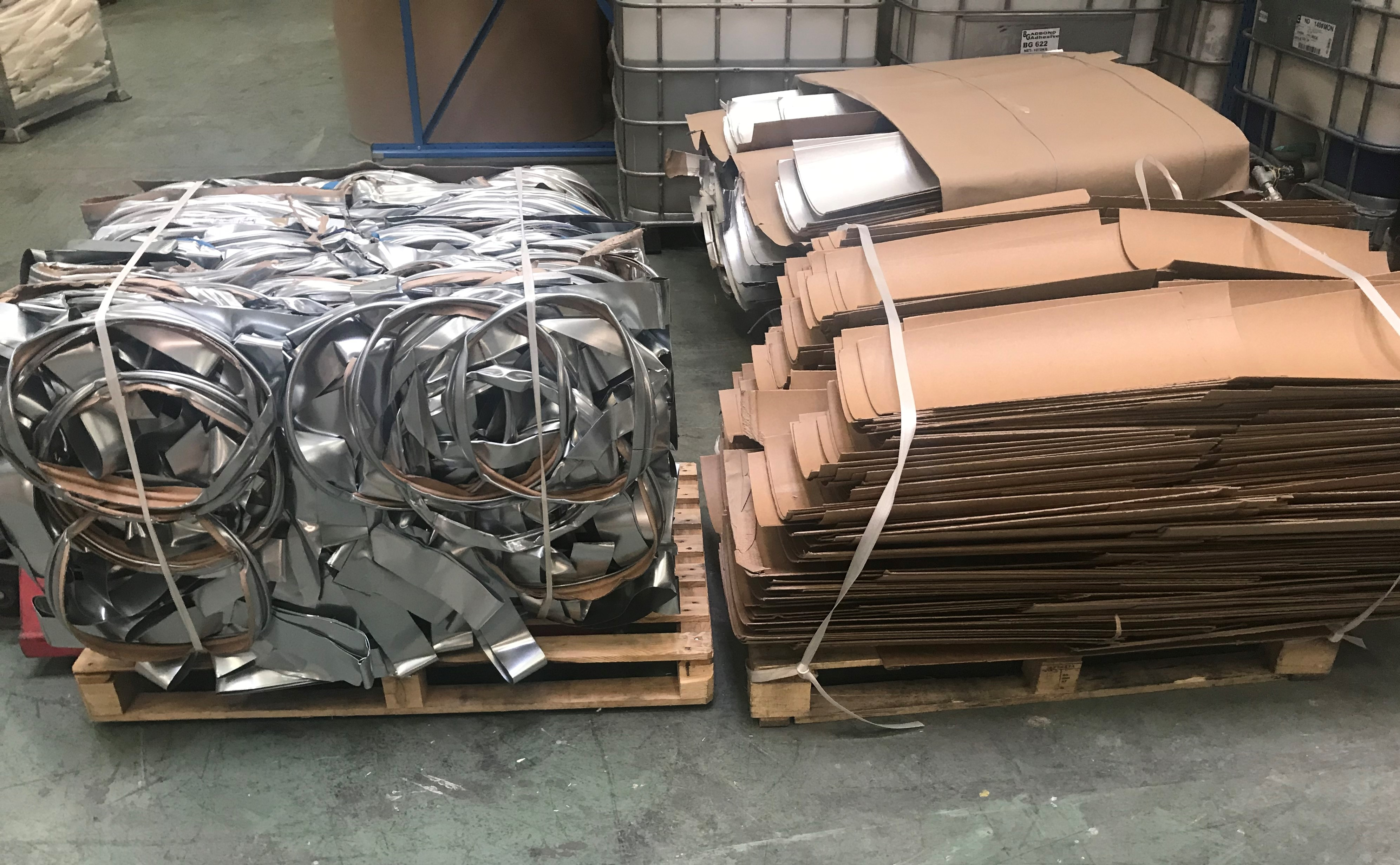 Two pallets packed with steel and paper components of used Enviroloc drums